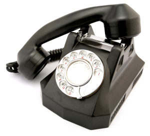 Photo of an old black rotary phone with the receiver off the hook.